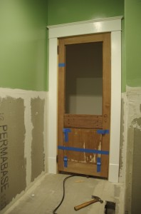 Bathroom door hung, trim installed, and backerboard installed.
